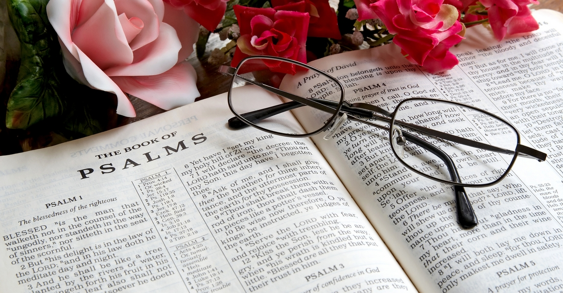 An open Bible with reading glasses lying on it.